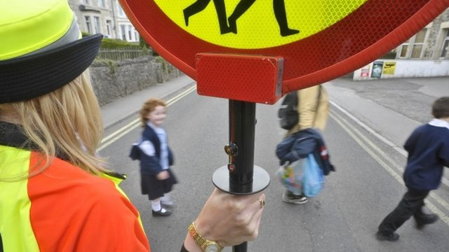 Children crossing the road with the help of a lollipop lady