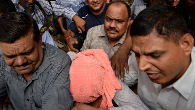 Indian policemen escort the accused