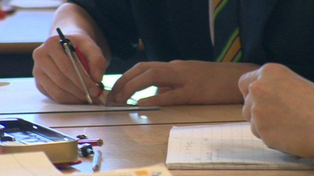 Hands of children working at desk