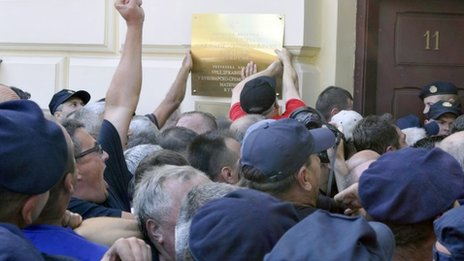 Protesters pull down a plaque from a local government building in Vukovar, eastern Croatia