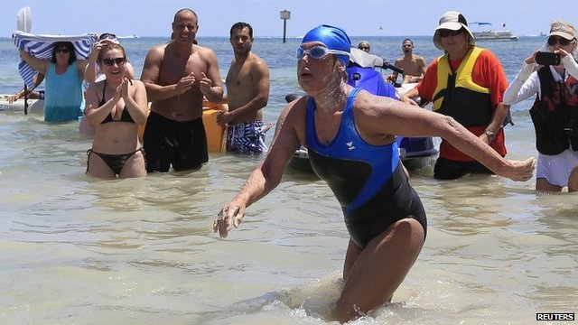 Diana Nyad , 64, walks to dry sand, completing her swim from Cuba as she arrives in Key West, Florida