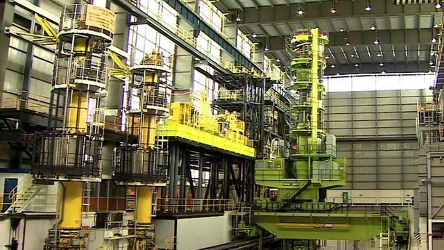 Inside a nuclear plant - a green spiral staircase and yellow walkway platform
