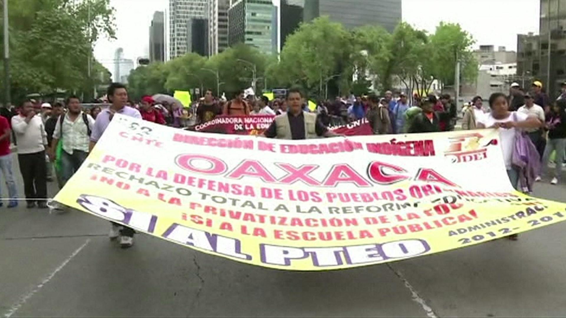 Protesters in Mexico City march with a banner opposing education reforms.