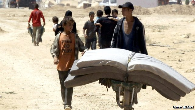 Boys moving mattresses around Zaatari refugee camp in Jordan