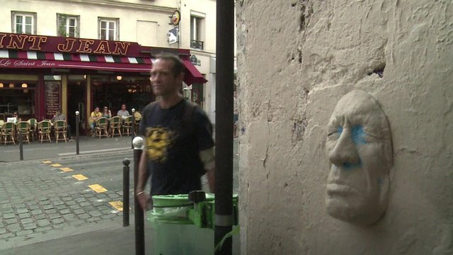 French artist Gregos walks past one of his face sculptures in Paris