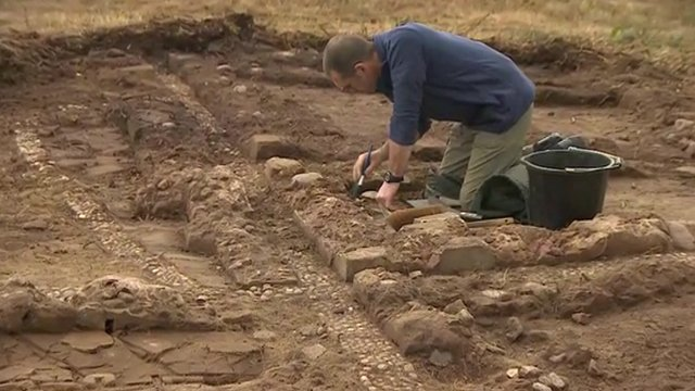 A volunteer works on excavating the training trench