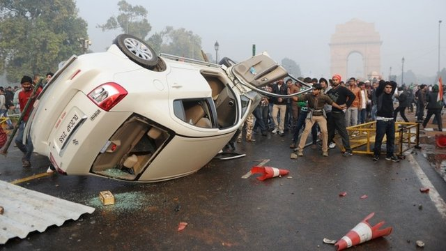 In December 2012, Indian demonstrators look on after turning over a car during a protest in front of the India Gate monument in New Delhi, calling for better safety for women following the rape of a student in the Indian capital