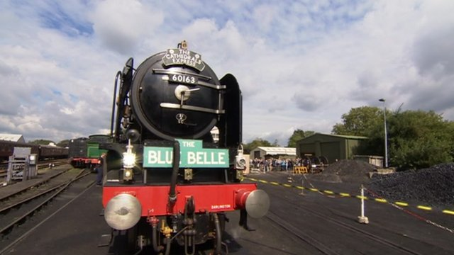 A steam locomotive arrives at Sheffield Park station