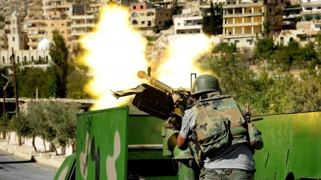 a Syrian military solider fires a heavy machine gun