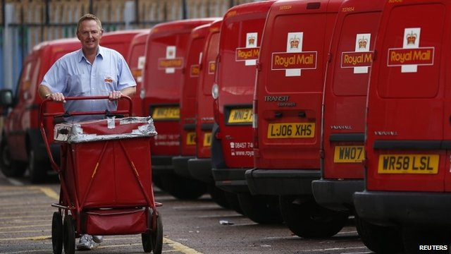 A postal worker pushes a cart at a Royal Mail sorting office in Loughborough
