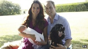 The Duke and Duchess of Cambridge sitting in a garden with their baby, Prince George, and two dogs