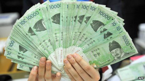 This photo taken on 1 February 2013 shows a bank employee holding South Korean won banknotes at the Korea Exchange Bank in Seoul