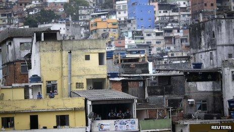 Police officers can be seen on the balcony of a house in Roncinha on 20 September, 2012