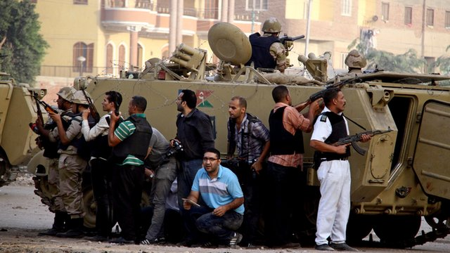 Egyptian security forces take cover during clashes with suspected militants (not pictured) in the town of Kerdasa