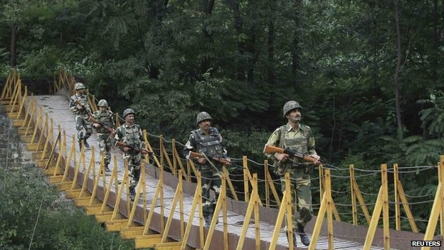 Border Security Force soldiers patrol a footbridge over a stream near the Line of Control (LoC) in Poonch district, on August 8, 2013