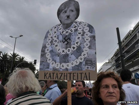 A Greek protestor holds a placard criticising Angela Merkel