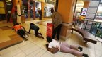 People scramble for safety as armed police hunt gunmen who went on a shooting spree at Westgate shopping centre in Nairobi on 21 September 2013.