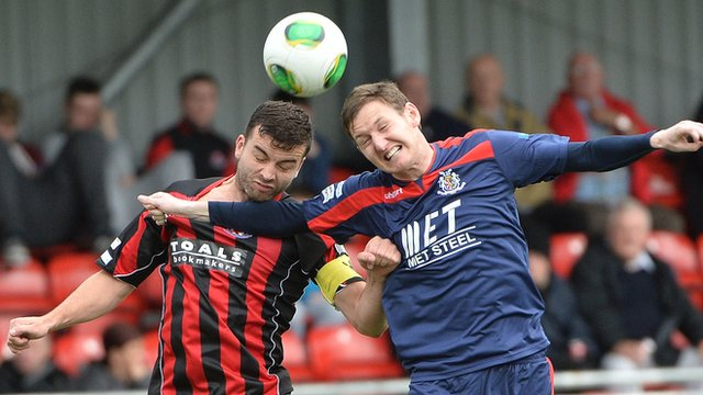 Crusaders Colin Coates challenges Portadown's Gary Twigg for the ball at Seaview