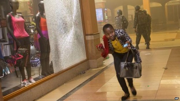 Woman who had been hiding during the gun battle flees after armed police enter the Westgate centre, Nairobi (21 September)