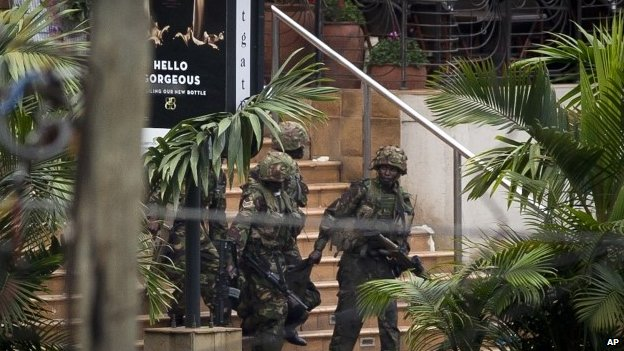 Soldiers from the Kenya Defense Force carry a wounded colleague out of the Westgate Mall