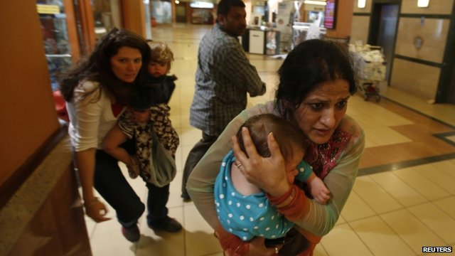 Women carrying children run for safety as armed police hunt gunmen who went on a shooting spree in Westgate shopping centre in Nairobi