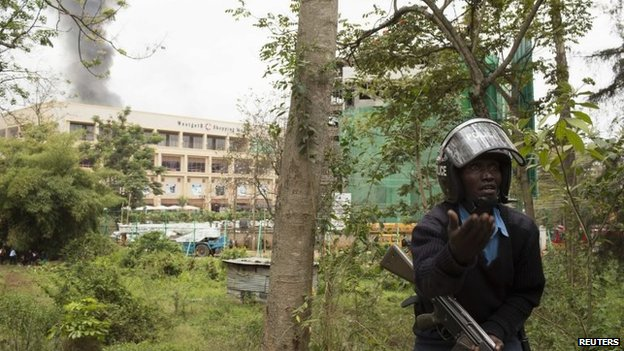 A security officer gestures as smoke rises from Westgate Shopping Centre