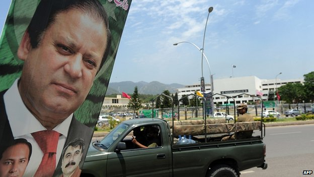 An army vehicle drives past a poster of Pakistan's Premier-elect Nawaz Sharif near parliament in Islamabad on June 5, 2013.