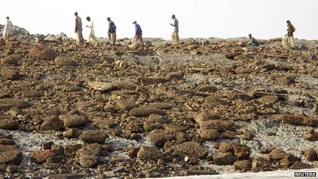 People walk on an island that rose from the sea following an earthquake, off Pakistan's Gwadar coastline in the Arabian Sea 25 September, 2013.