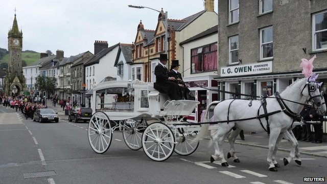 The coffin of April Jones is carried by a horse-drawn carriage