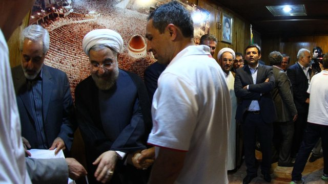 Omid Namazi shakes hands with Iranian president Hassan Rouhani in Tehran.