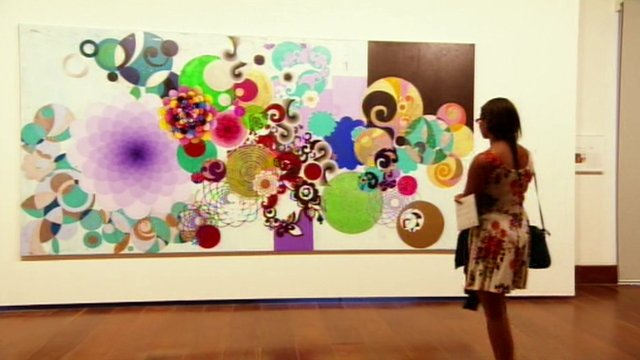 A woman admires a painting in Brazil