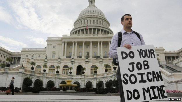 A furloughed federal employee holds a sign on the steps to the US Capitol after the US government shut down last night, on Capitol Hill in Washington on 1 October 2013.