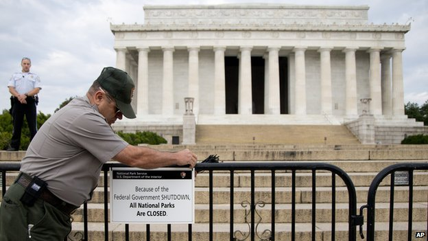 A US Park Police officer watches at left as a National Park Service employee posts a sign on a barricade closing access to the Lincoln Memorial in Washington on 1 October 2013.