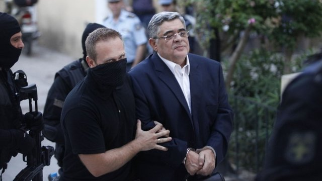 Far-right Golden Dawn party leader Nikos Mihaloliakos (R) is escorted by anti-terrorism police officers as he arrives at a courthouse in Athens