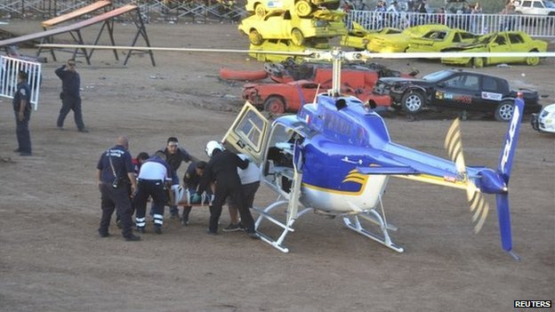 An injured spectator is wheeled by paramedics to a helicopter.