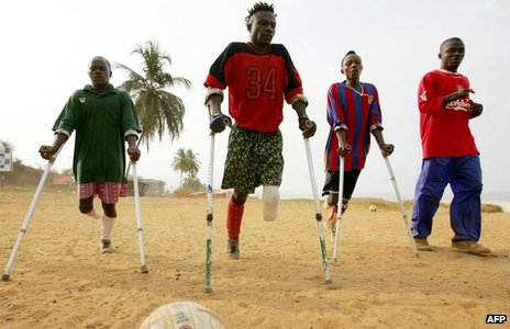 Players of the Sierra Leone civil war amputees football team pose on 7 April 2006 at a beach in Freetown, Sierra Leone