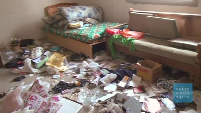A room with scattered belongings on the floor