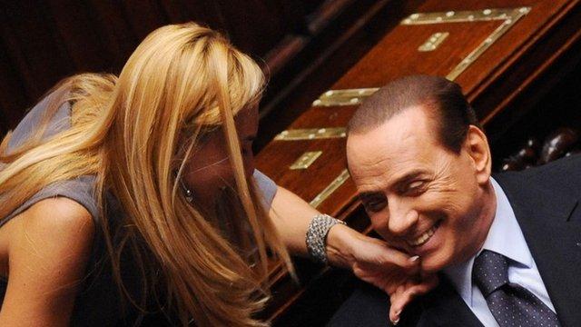 """Italian MP Michaela Biancofiore (L) squeezes Italian Prime Minister Silvio Berlusconi""""s chin at the Parliament in Rome, 3 August 2011"""