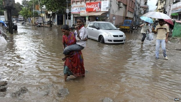 A woman in the Indian city of Hyderabad carries her son across a flooded street