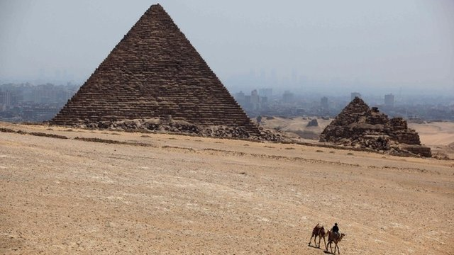 A man rides a camel past Khufu pyramid, the largest of pyramids at the historical site of the Giza Pyramids, near Cairo, Egypt