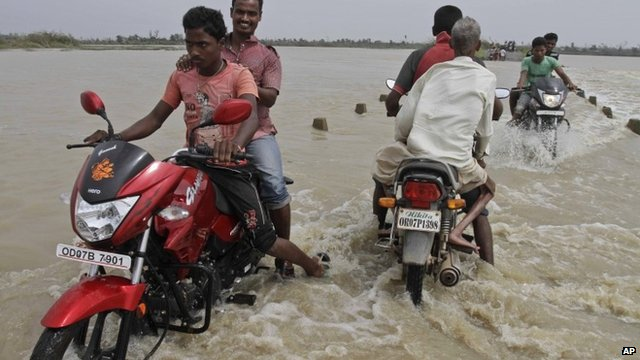 People ride over a flooded bridge after Cyclone Phailin struck Berhampur, in the eastern Indian state of Orissa