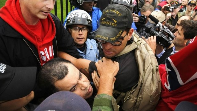 Protesters try to disengage some of their fellow demonstrators from a confrontation with law enforcement as they climb the wall and fence in front of the White House gates in Washington
