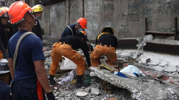 Rescuers shift through the rubble to recover an unidentified man at a fish port in Pasil, Cebu, central Philippines, 15 October 2013