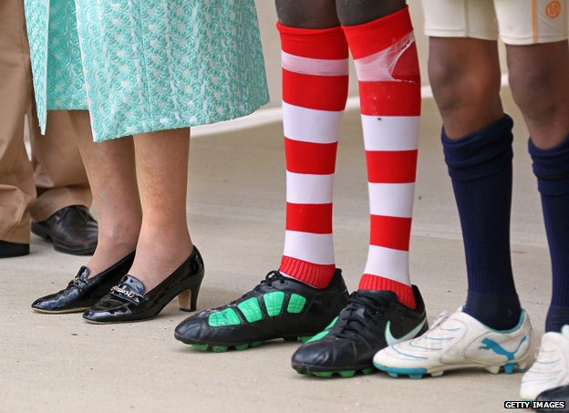 The Queen and two footballers stand