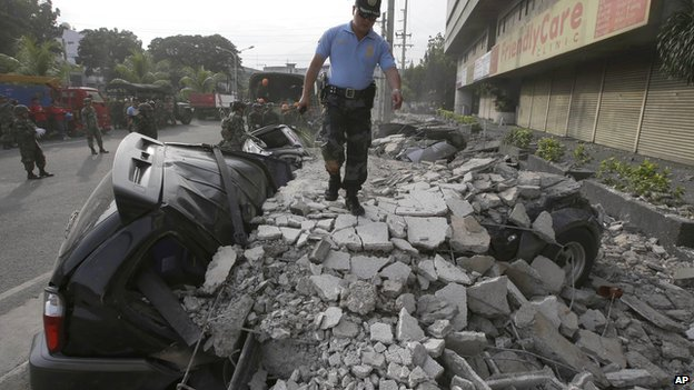 A police officer surveys the damage following a 7.2-magnitude earthquake that hit Cebu city