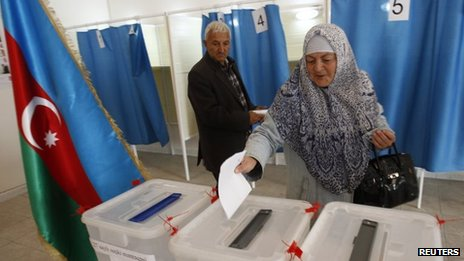 A woman casts her vote during the presidential elections at the polling station in the village of Nardaran