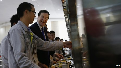 George Osborne talks with workers as they collect food at a canteen near Taishan (17 Oct 2013)