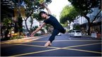 ballet dancer leaping in middle of Singapore road