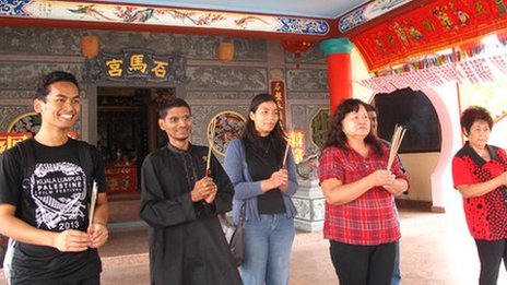 People of different religions burning incense at a Chinese temple