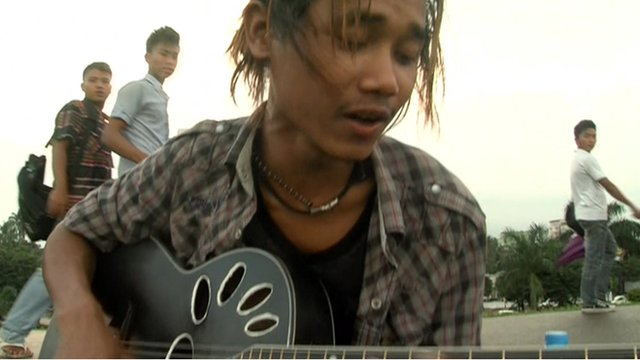 Young man playing guitar in the street